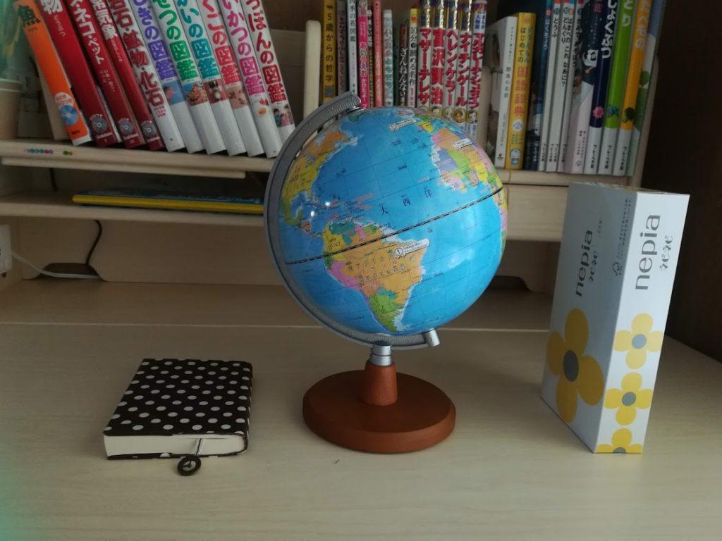 横一列に並べられた地球儀と文庫本とボックスティッシュ